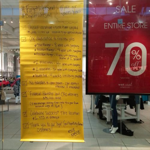 Employees leave a protest sign at failing Wet Seal mall store in Seattle
